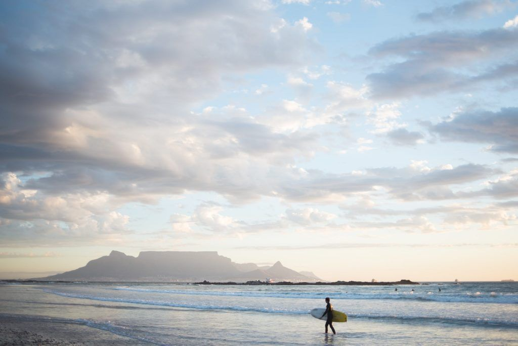 Surfer walking along the shore of Cape Town, South Africa