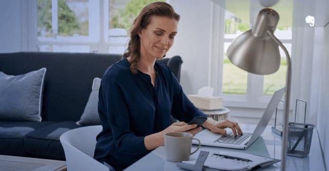 Foto de uma mulher trabalhando no home office, mexendo em um computador e em um celular