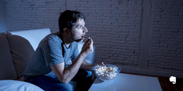 homem na frente da tv comendo pipoca