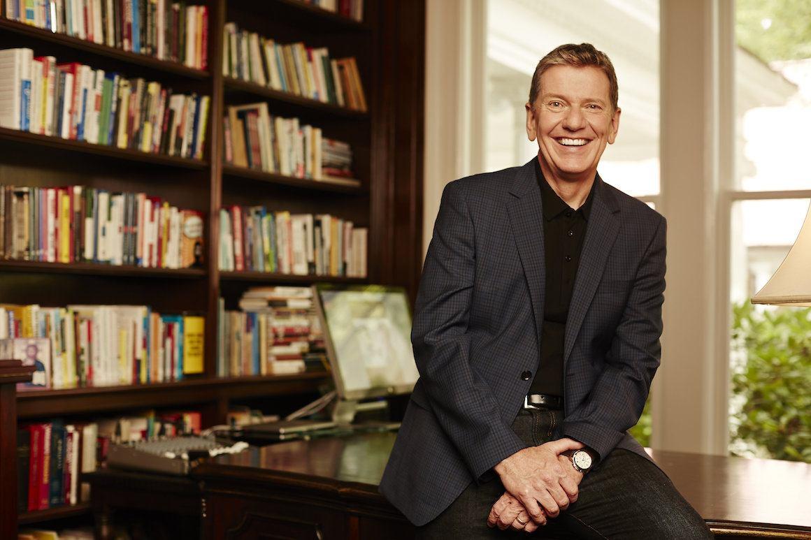 Michael Hyatt Sitzend auf einem Schreibtisch vor einem Büchergestell