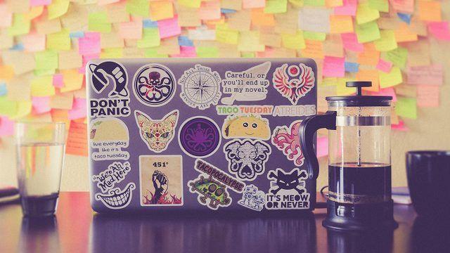 Foto de um laptop coberto de adesivos e uma garrafa de café ao lado