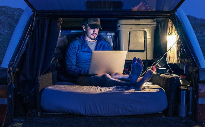 Man sitting in truck working on laptop