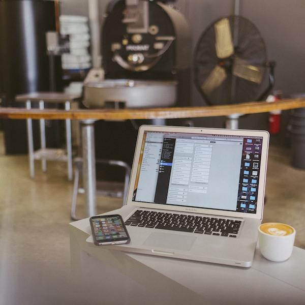 MacBook con café y teléfono inteligente