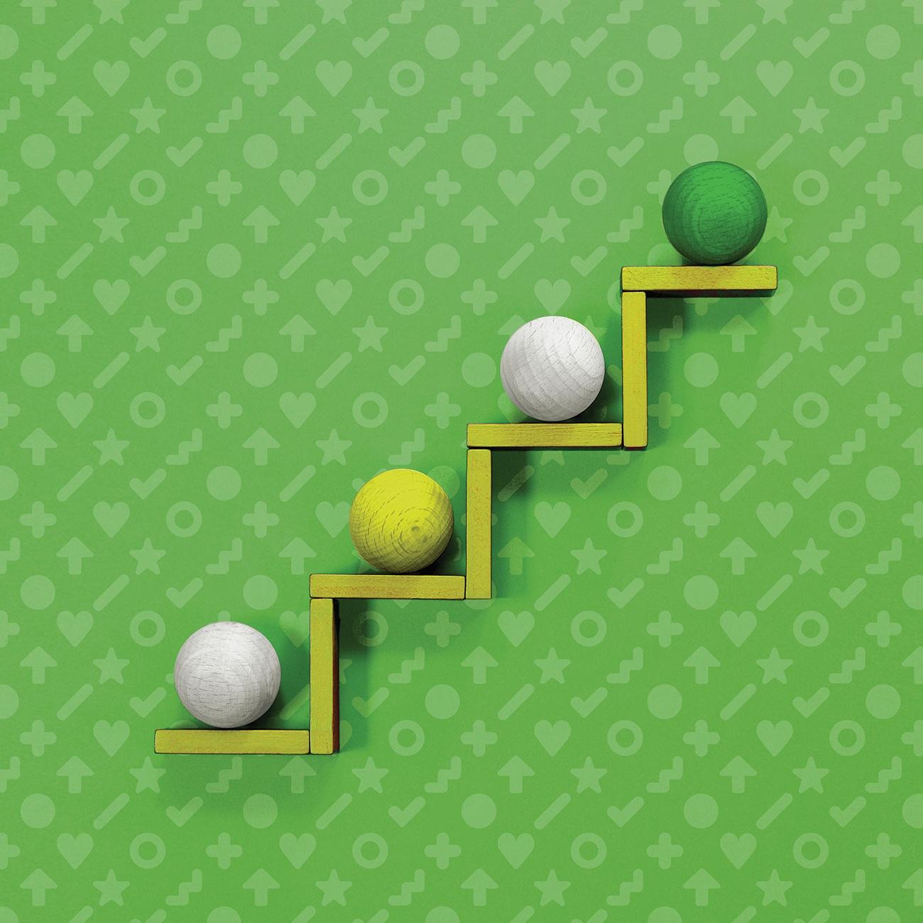 Four wooden balls on a rising platform, set against a patterned background.