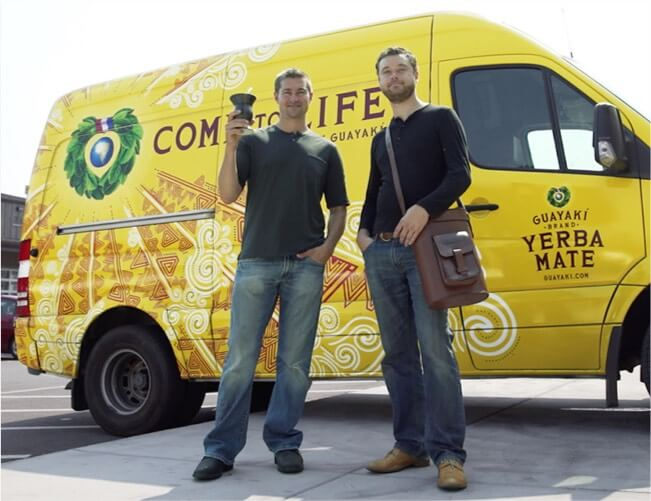 Two people standing next to a yellow van with Guayaki branding