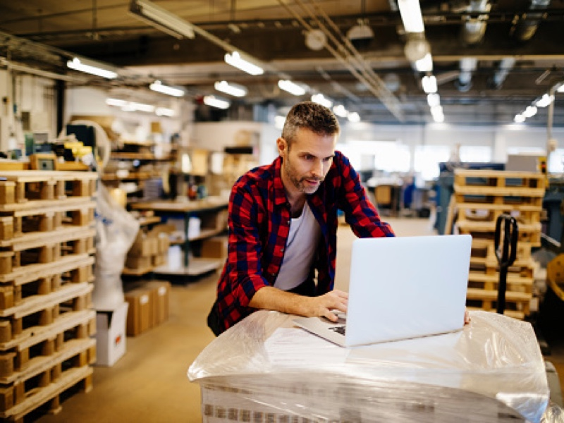 Image of warehouse worker using laptop, depicting the way cloud-based document management lets people to work from anywhere